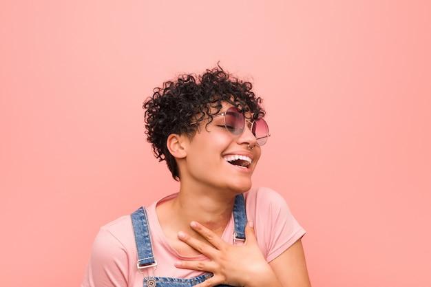 De jonge gemengde afrikaanse amerikaanse tienervrouw lacht luid het houden van hand op borst.