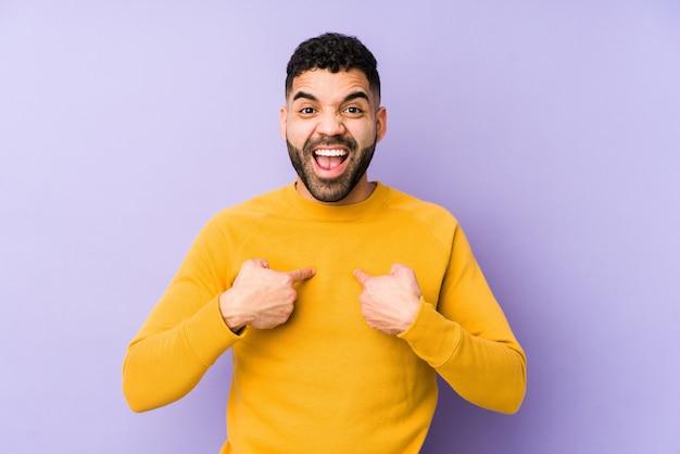 De jonge gemengde ras arabische mens isoleerde verrast wijzend met vinger, breed glimlachend.