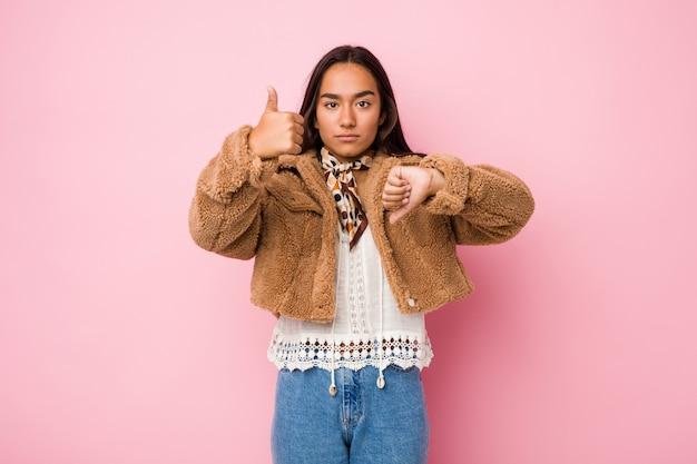 De jonge gemengde ras indische vrouw die een korte schapehuid dragen die duimen omhoog en duimen coatshowing, kiest concept moeilijk