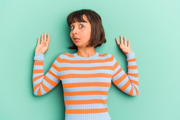 De jonge gemengde rasvrouw die op blauwe achtergrond wordt geïsoleerd geeft met beide voorvingers aan die een lege ruimte tonen.