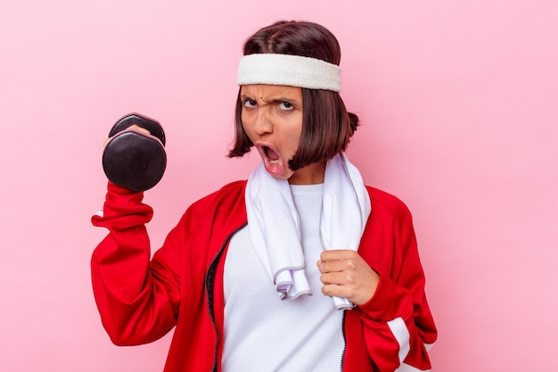 De jonge gemengde vrouw die van de rassport een gewicht houdt dat op roze muur wordt geïsoleerd