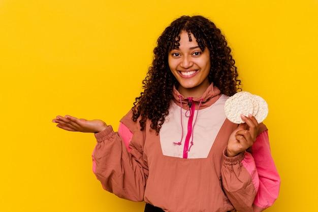 De jonge gemengde vrouw die van de rassport een rijstkoekjes houdt die op gele muur worden geïsoleerd die een exemplaarruimte op een palm toont en een andere hand op taille houdt.
