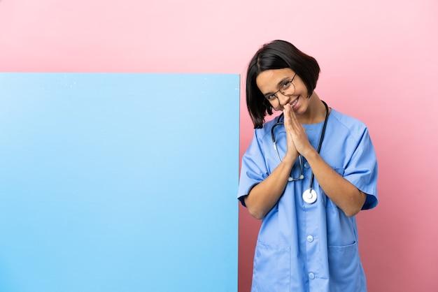 De jonge gemengde vrouw van de raschirurg met een grote banner over geïsoleerde achtergrond houdt de palm bij elkaar. persoon vraagt om iets