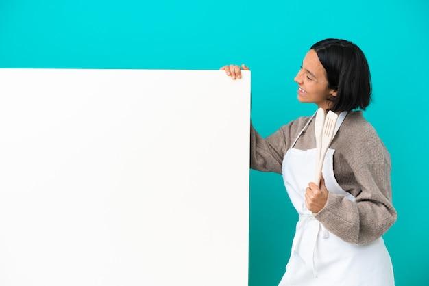 De jonge gemengde vrouw van de raskok met een groot aanplakbiljet dat op blauwe achtergrond in zijpositie wordt geïsoleerd