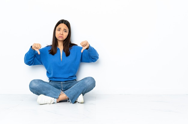 De jonge gemengde zitting van de rasvrouw op de vloer die op witte muur wordt geïsoleerd die duim neer met twee handen toont