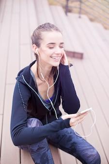 De jonge geschikte sportieve vrouw rust en luistert muziek op mobiele telefoon na opleiding