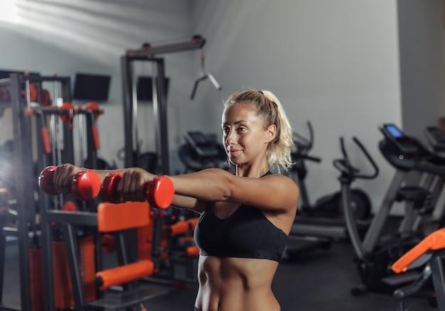 De jonge geschikte vrouw in sportkleding leidt met domoren in de gymnastiek op. gezonde levensstijl concept. lichaamstraining met vrije gewichten