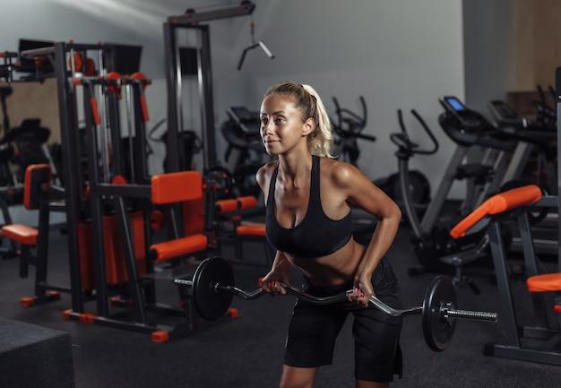 De jonge geschikte vrouw in sportkleding leidt met een barbell op in de gymnastiek. gezonde levensstijl concept. lichaamstraining met vrije gewichten