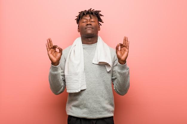 De jonge geschiktheids afrikaanse zwarte mens ontspant na harde werkdag, voert hij yoga uit.