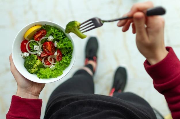 De jonge geschiktheidsvrouw in tennisschoenen eet een gezonde salade na een training. fitness en gezonde levensstijl concept