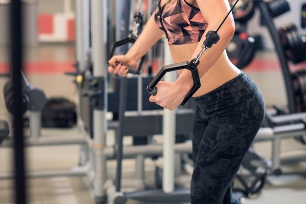 De jonge geschiktheidsvrouw voert oefening met oefeningsmachine kabeloversteekplaats in gymnastiek uit