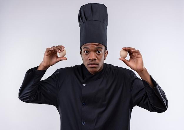 De jonge geschokte afro-amerikaanse kok in eenvormige chef-kok houdt eieren aan beide handen die op witte muur worden geïsoleerd