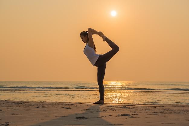 De jonge gezonde vrouw het praktizeren yoga stelt op het strand bij zonsopgang.