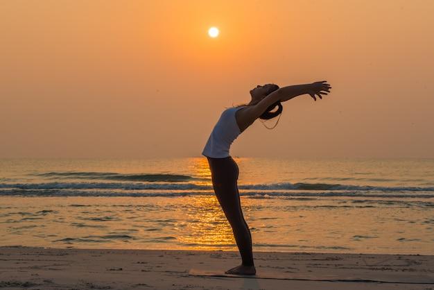 De jonge gezonde yogavrouw het praktizeren yoga stelt op strand in de ochtend