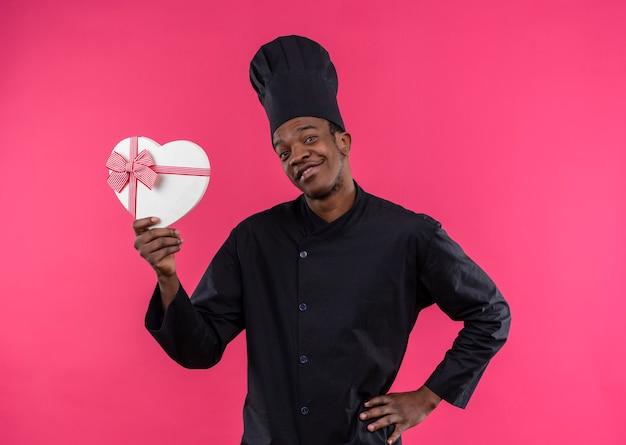 De jonge glimlachende afro-amerikaanse kok in eenvormige chef-kok houdt de doos van de hartvorm die op roze muur wordt geïsoleerd