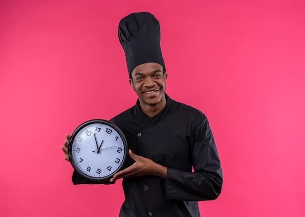 De jonge glimlachende afro-amerikaanse kok in eenvormige chef-kok houdt klok die op roze muur wordt geïsoleerd