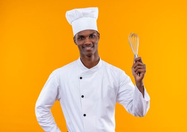 De jonge glimlachende afro-amerikaanse kok in eenvormige chef-kok houdt klopper en legt hand op taille die op oranje muur wordt geïsoleerd