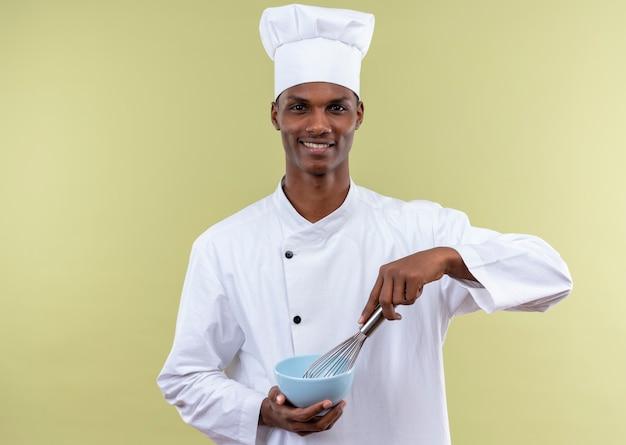 De jonge glimlachende afro-amerikaanse kok in eenvormige chef-kok houdt kom en zwaait geïsoleerd op groene muur