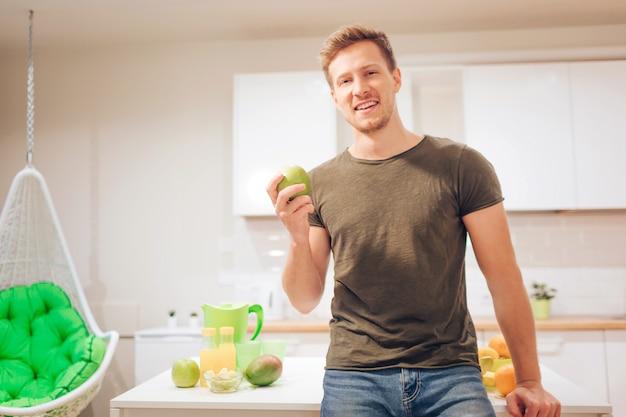 De jonge glimlachende knappe mens houdt organische appel terwijl het snijden van vers fruit in de keuken.
