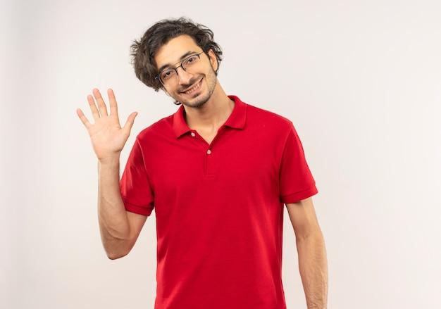De jonge glimlachende mens in rood overhemd met optische bril werpt hand op die op witte muur wordt geïsoleerd