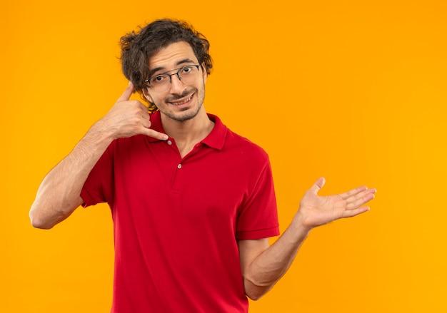 De jonge glimlachende mens in rood overhemd met optische brilgebaren noemt me handteken en wijst aan kant geïsoleerd op oranje muur
