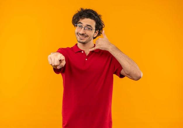 De jonge glimlachende mens in rood overhemd met optische glazen gebaren noemt me handteken en punten die op oranje muur worden geïsoleerd