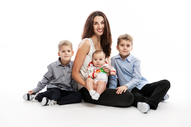 De jonge glimlachende moeder met drie kinderen zit op een witte muur. een blije familie.