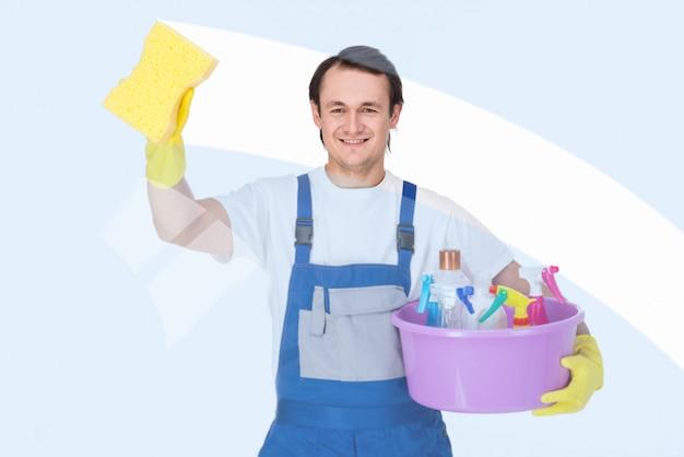 De jonge glimlachende schonere mens maakt vensters schoon.