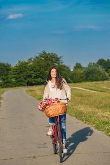 De jonge glimlachende vrouw berijdt een fiets met een mandhoogtepunt van bloemen op platteland