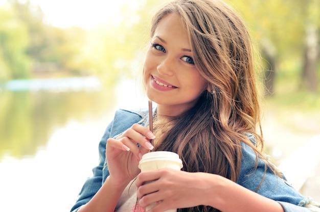 De jonge glimlachende vrouw drinkt een koffie buiten in de herfstpark