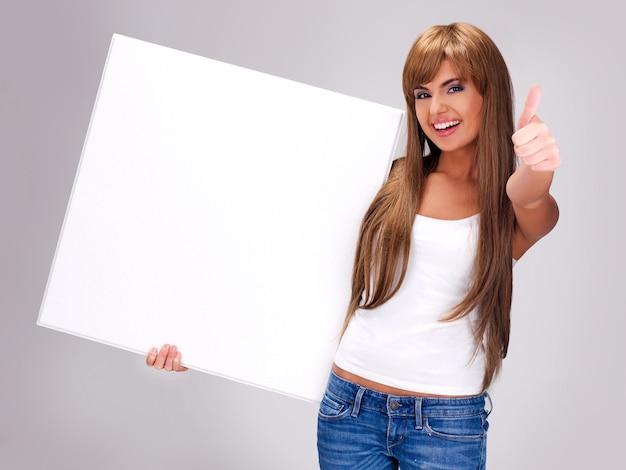 De jonge glimlachende vrouw houdt wit groot aanplakbiljet met duimen omhoog gebaar