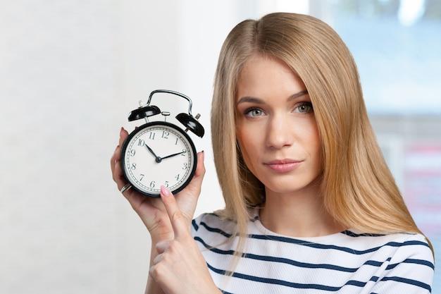 De jonge glimlachende vrouw houdt zwarte klok