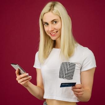 De jonge glimlachende vrouw koopt online. houdt een smartphone en een creditcard in de hand op robijn