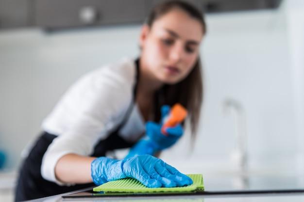 De jonge glimlachende vrouw maakt de keuken bij haar huis schoon
