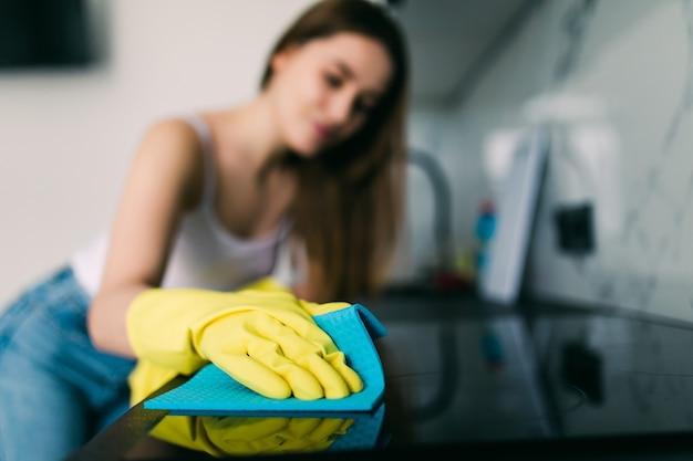De jonge glimlachende vrouw maakt de keuken bij haar thuis schoon