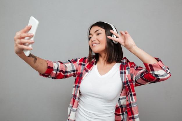 De jonge glimlachende vrouw maakt selfie over grijze muur.