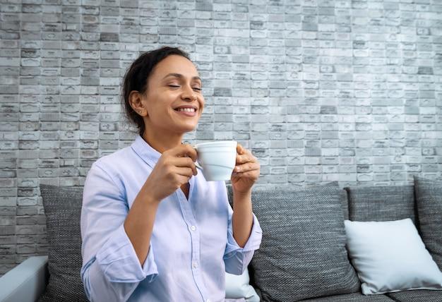 De jonge glimlachende vrouw met een kopje koffie in haar handen zittend op de bank.