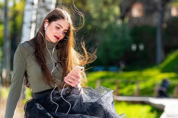 De jonge glimlachende vrouw zit op bank in park in openlucht luisterend muziek met hoofdtelefoons gebruikend mobiele telefoon op een zonnige en winderige dag
