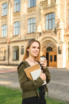 De jonge glimlachende vrouwelijke studentenholding haalt koffie in het park dichtbij het college weg