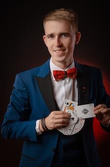 De jonge goochelaar houdt kaarten in zijn handen