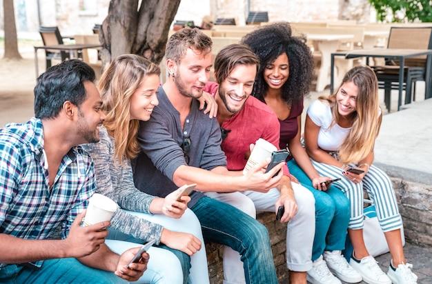 De jonge groep van studentenvrienden gebruikt smartphone met koffie bij universitaire universiteit