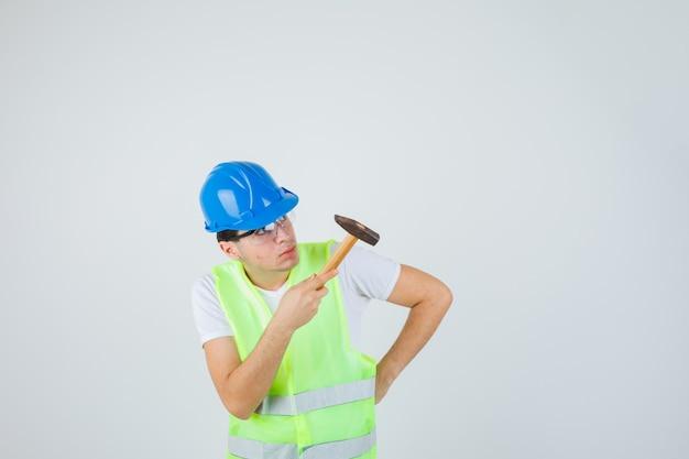 De jonge hamer van de jongensholding, hand op taille zetten, hamer in bouwuniform bekijken en geconcentreerd kijken. vooraanzicht.