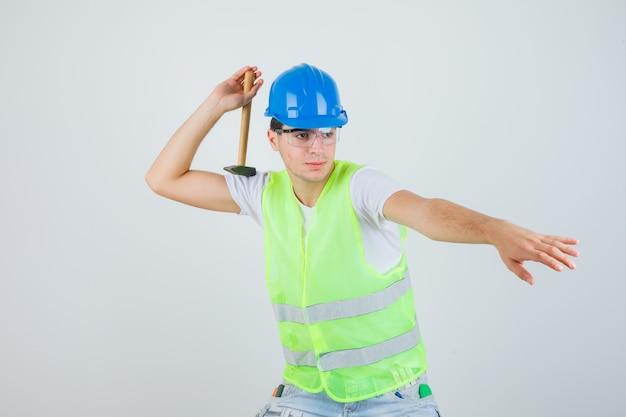 De jonge hamer van de jongensholding, probeert het in bouwuniform te gooien en kijkt gefocust, vooraanzicht.
