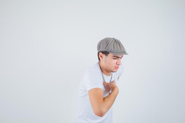 De jonge hand van de jongensholding op borst in t-shirt, hoed en peinzend kijkt. vooraanzicht.