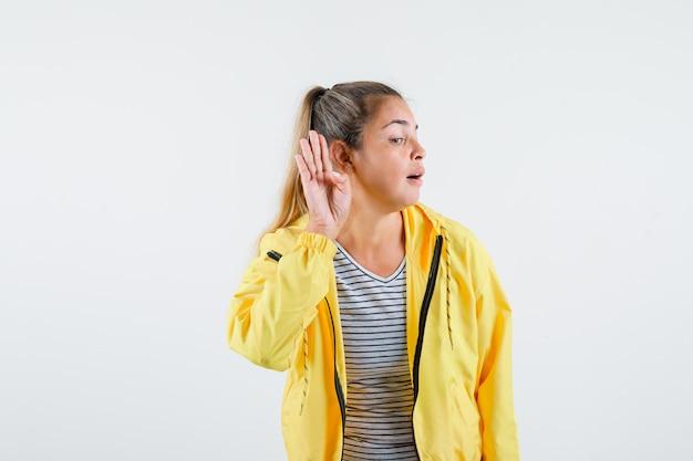 De jonge hand van de vrouwenholding dichtbij oor in t-shirt, jasje en nieuwsgierig kijkt. vooraanzicht.