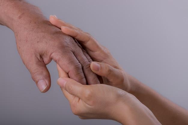 De jonge hand van de vrouwenholding van haar grootvader over grijze achtergrond. nationale seniorendag.