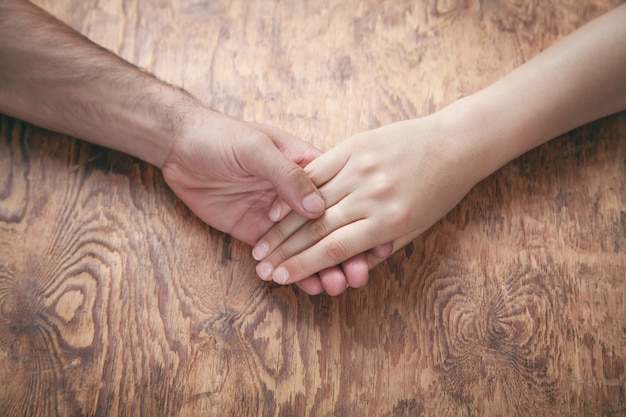 De jonge handen van de paarholding op houten achtergrond