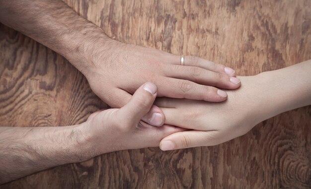 De jonge handen van de paarholding op houten