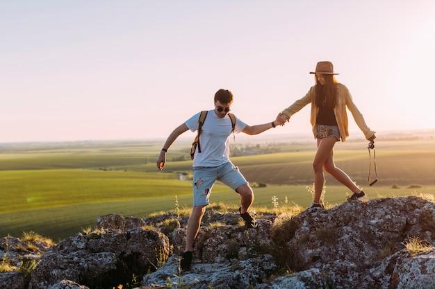 De jonge handen van de paarholding terwijl wandeling op rots