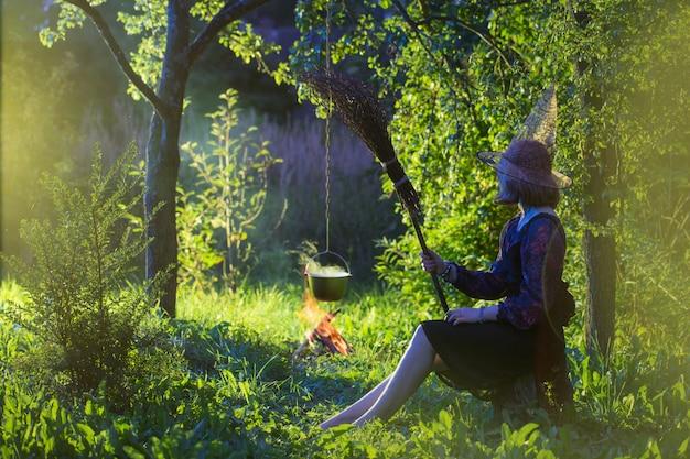 De jonge heks door brand in magisch bos maakt in ketel toverdrank